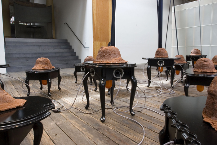 Second Nature (detail); Paul Stout; 20 tables, plastic, soil, resin covered mounds with protruding roots, circuit boards, wire, motor, steel blade and mechanical components inside; dimensions variable, tables: 24 x 30 x 18