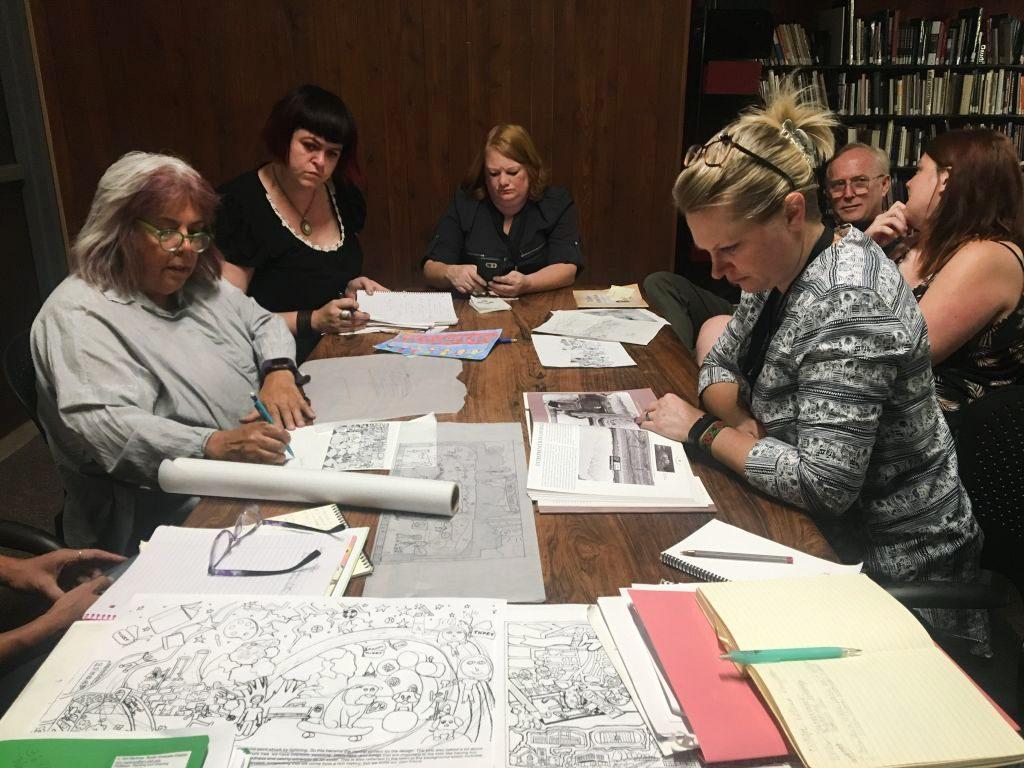 Professor Kim Martinez presents maquette drawings of the mural designs to Murray City representatives
